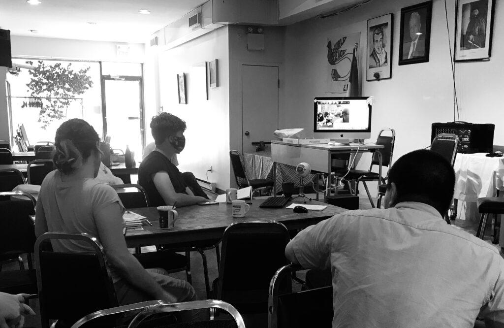 Des camarades de Toronto sont assis dans la salle grecque devant des photos de Nikos Beloyannis et Aris Velouchiotis